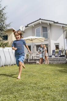 Boy running in garden with parents watching - DIGF08237
