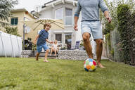 Father and son playing football in garden - DIGF08240