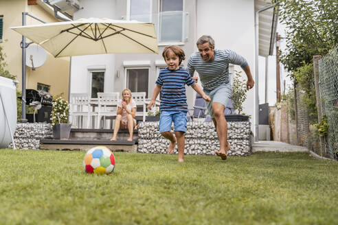 Father and son playing football in garden - DIGF08243