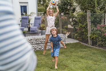 Happy family playing football in garden - DIGF08246