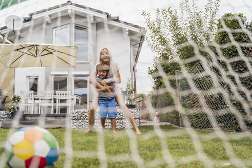 Happy mother and son playing football in garden - DIGF08249