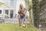 Happy mother and son playing football in garden - DIGF08252