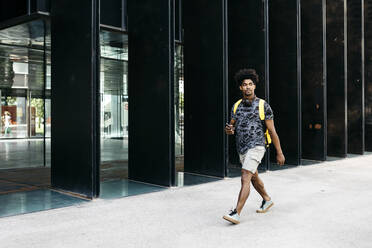 Man with yellow backpack, smartphone and headphones walking down the street, Barcelona, Spain - JRFF03687