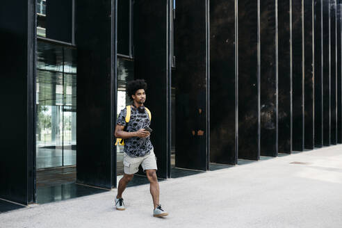 Man with yellow backpack, smartphone and headphones walking down the street, Barcelona, Spain - JRFF03690