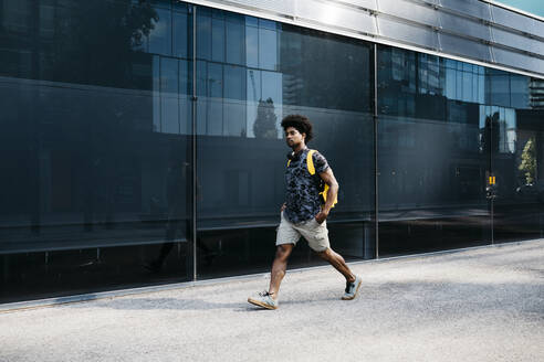 Man with yellow backpack and headphones walking down the street, Barcelona, Spain - JRFF03696