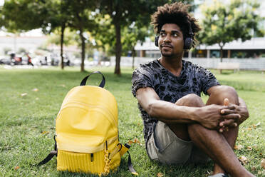 Portrait of man sitting on a meadow listening music with cordless headphones, Barcelona, Spain - JRFF03705