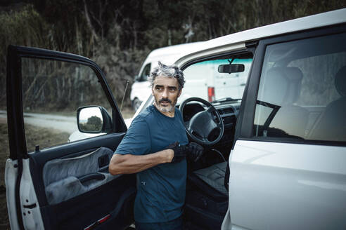 Mature man standing at his off-road vehicle - OCMF00640