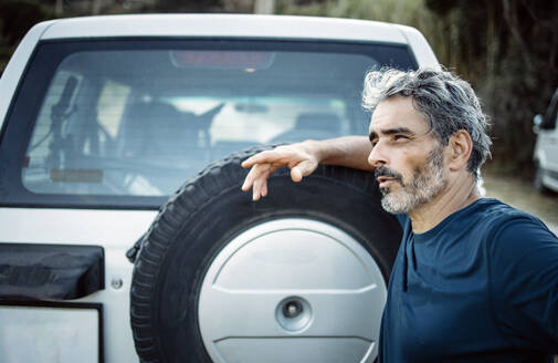 Mature man standing at his off-road vehicle - OCMF00643