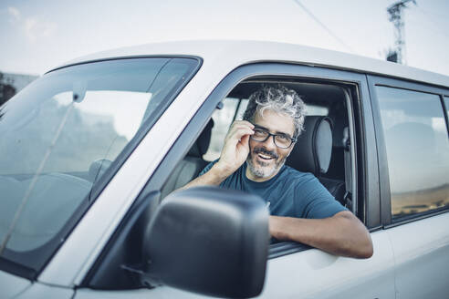 Smiling mature man sitting in his off-road vehicle - OCMF00646