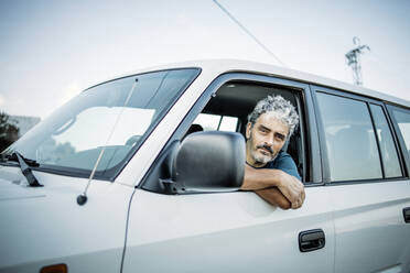 Mature man sitting in his off-road vehicle - OCMF00649