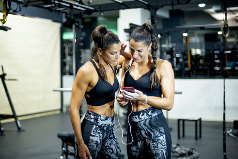 Twin happy sisters in gym with smartphone and headphones - OCMF00653