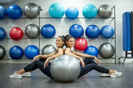 Portrait of smiling twin sisters sitting on the floor in gym with a fitness ball - OCMF00656