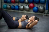 Twin sisters training in gym doing sit-ups - OCMF00662