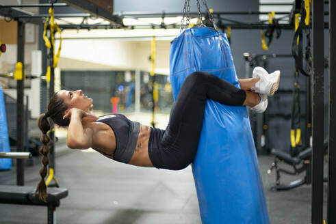 Young woman training hanging on punching bag in gym - OCMF00665