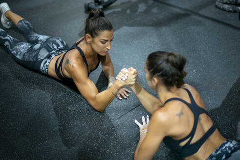 Twin sisters doing arm wrestling in gym - OCMF00668