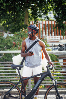 Happy bicycle courier with cell phone looking around - OCMF00674