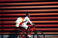 Bicycle courier delivering a teddy bear passing a red wall - OCMF00692