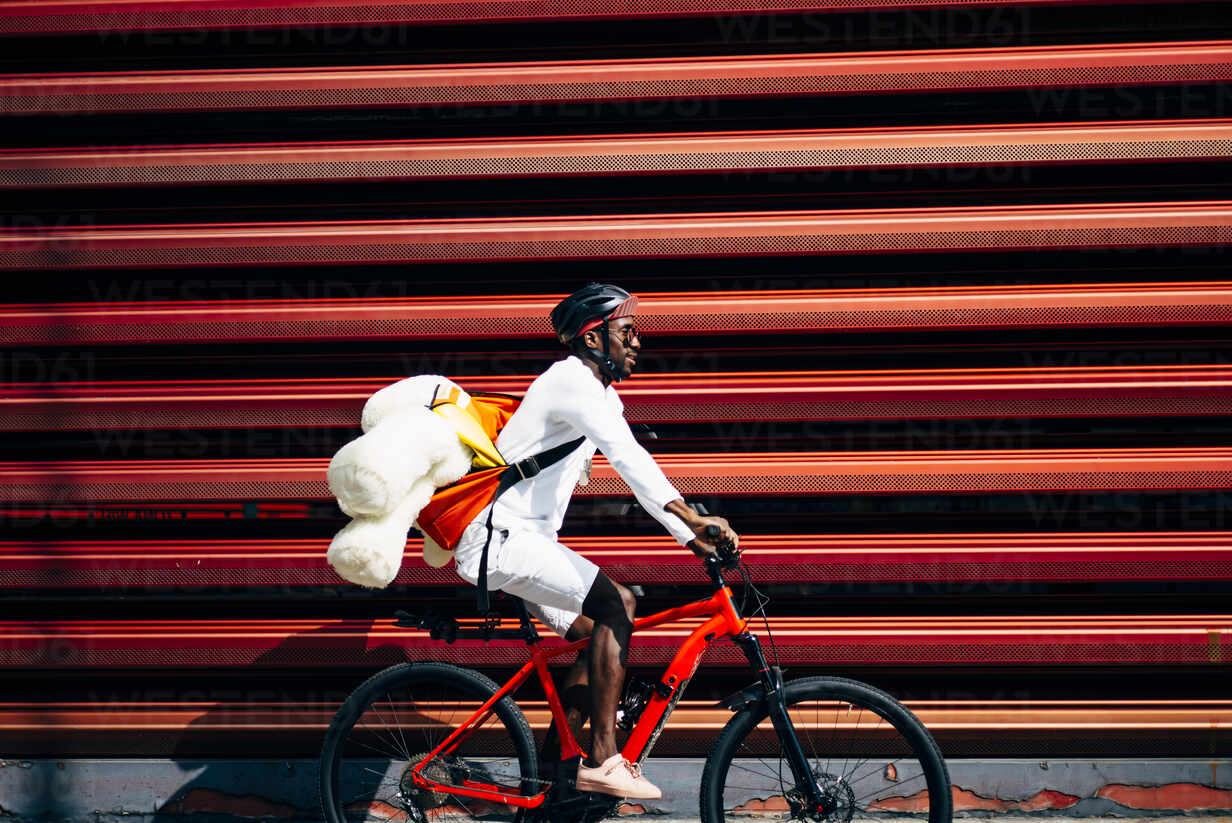 Bicycle courier delivering a teddy bear passing a red wall - OCMF00692 - Oscar Carrascosa Martinez/Westend61