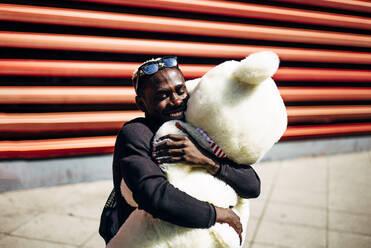 Happy young man hugging huge teddy bear - OCMF00695