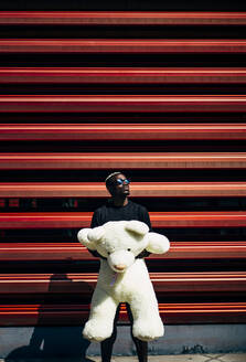 Portrait of cool young man holding huge teddy bear - OCMF00698