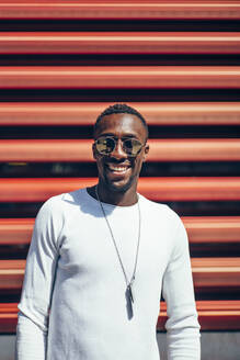 Portrait of smiling young man standing at a red wall - OCMF00701