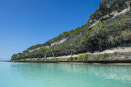 The grey Lekiny cliffs by turquoise sea against clear sky, Ouvea, Loyalty Islands, New Caledonia - RUNF03063