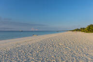 White sand beach at sunset against sky in Ouvea, Loyalty Islands, New Caledonia - RUNF03072