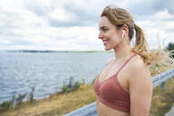 Portrait of smiling sporty woman with wireless earphones at the lakeside - BSZF01388