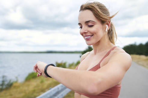 Portrait of fit woman checking smartwatch during outdoor jogging session - BSZF01391