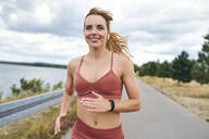 Portrait of smiling athletic woman jogging outdoors - BSZF01397