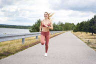 Smiling athletic woman jogging near lake - BSZF01400