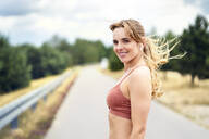 Portrait of smiling sporty woman with wireless earphones in nature - BSZF01403