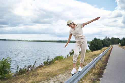 Happy woman balancing on crash barrier at the lakeside - BSZF01409