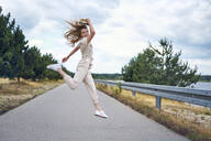 Cheerful woman jumping on rural road - BSZF01424