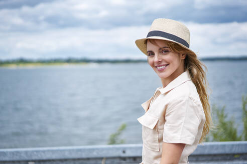 Portrait of smiling woman with hat at the lakeside - BSZF01430