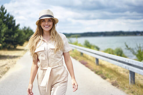 Portrait of smiling woman walking on rural road at the lakeside - BSZF01433