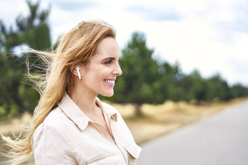 Portrait of happy woman with wireless earphones in nature - BSZF01436