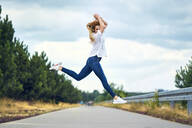 Cheerful woman jumping on rural road - BSZF01439