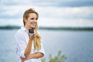 Happy woman using cell phone at the lakeside - BSZF01445