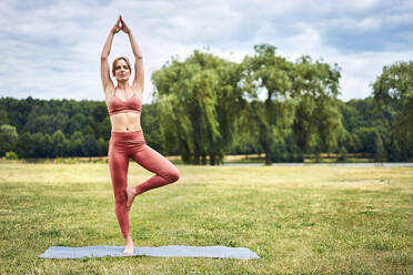 Athletic woman doing tree yoga pose during training session in the park - BSZF01448