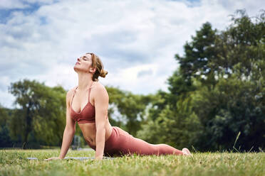 Woman doing cobra pose during yoga training in the park - BSZF01451