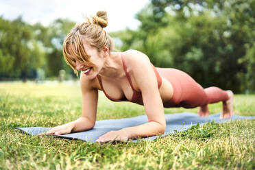 Athletic woman doing plank exercises outdoors in the park - BSZF01457