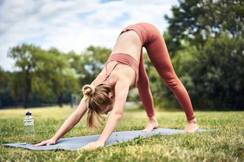 Woman practicing yoga in park doing downward facing dog pose - BSZF01460