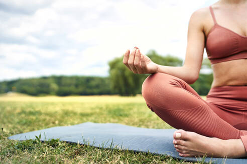 Close-up of woman practicing yoga in park - BSZF01463