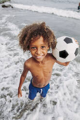 Portrait of a smiling boy holding a football on the beach - LJF00978