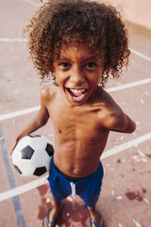 Portrait of a boy holding a soccer ball standing on a soccer field - LJF00981