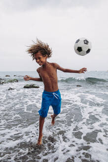Boy playing with a football on the beach - LJF00987