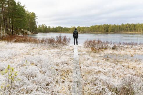 Mature woman standing in front of Lake Lillskiren in Sweden - FOLF10826
