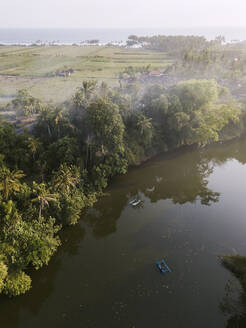 Aerial view of boats on river by land in Bali, Indonesia - KNTF03347