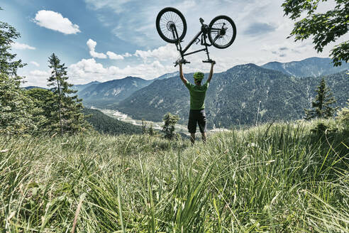 Mountain biker in the mountains holding up his mountain bike, Bavaria, Germany - WFF00089